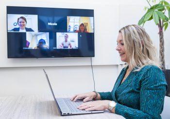 Vrouw achter laptop online pratend met mensen