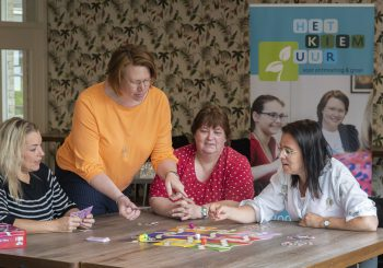 Drie vrouwen aan tafel kijken naar spel op tafel met een vrouw staand naast de tafel